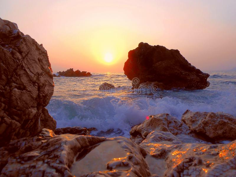 Orphic, mystical, arcane sunset, pink sky. Bright colorful sunset on the sea on a wild beach, stones boulders of red-brown color, glare of water, waves, sea stock photography