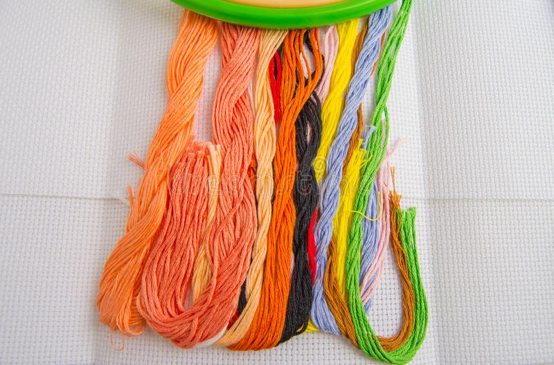 Bright colorful thread for embroidery thread on canvas. Handmade accessories on white background. Place for text, top view.  stock photo