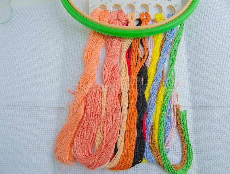 Bright colorful thread for embroidery thread on canvas. Handmade accessories on white background. Place for text, top view.  stock image