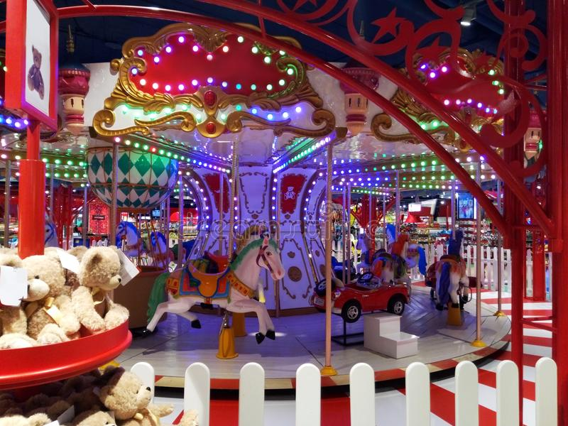 Bright and colorful toy store with children`s carousel in the center closeup stock photos