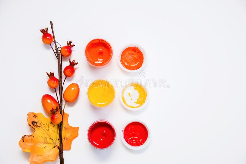 Bright colors of autumn, open acrylic paints and a decorative twig with berries and a leaf on white background, close-up, copy. Space, flat lay royalty free illustration