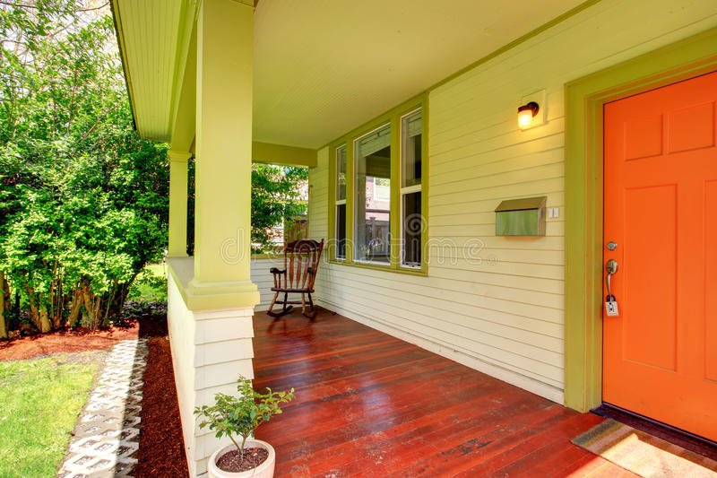 Bright colors porch. Open green porch with orange entrance door and rocking chair stock photo