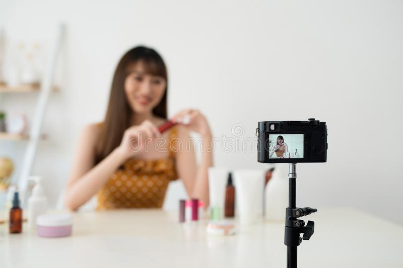 Bright colour. Nice happy woman showing a shiny lipstick while recording a video for her blog.  royalty free stock photography