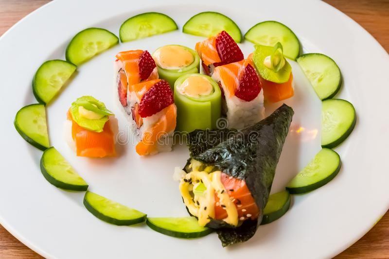 Bright colour Sushi with fruit. And cucumber on a white plate royalty free stock photography