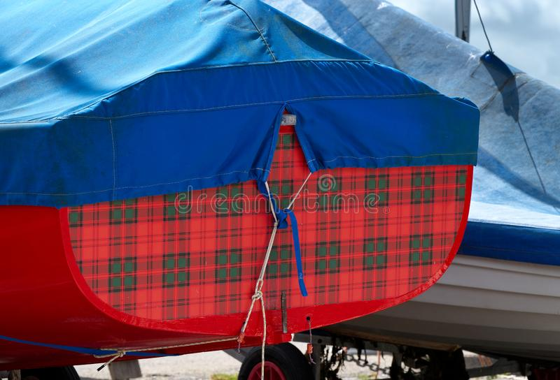 Bright coloured design on stern of sailing dinghy. The tartan style stern of a sailing dinghy,  contrasts with it`s blue weather cover. Bosham Quay, West Sussex stock images