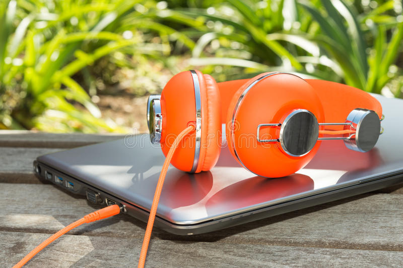 Bright coloured orange headphones and mobile compu royalty free stock photos