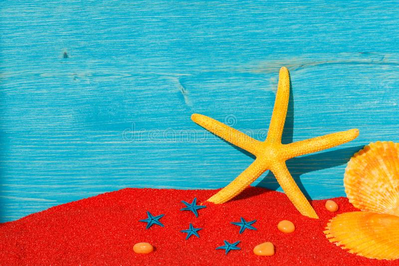 Bright colourful background with yellow starfish end red sand. Bright colourful picture with yellow starfish, red sand, two orange seashells and a blue wooden royalty free stock images