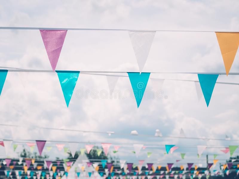 Bright colourful flags on the rope against clouds during summer festival. Cheerful colourful decoration at country summer festival royalty free stock photography