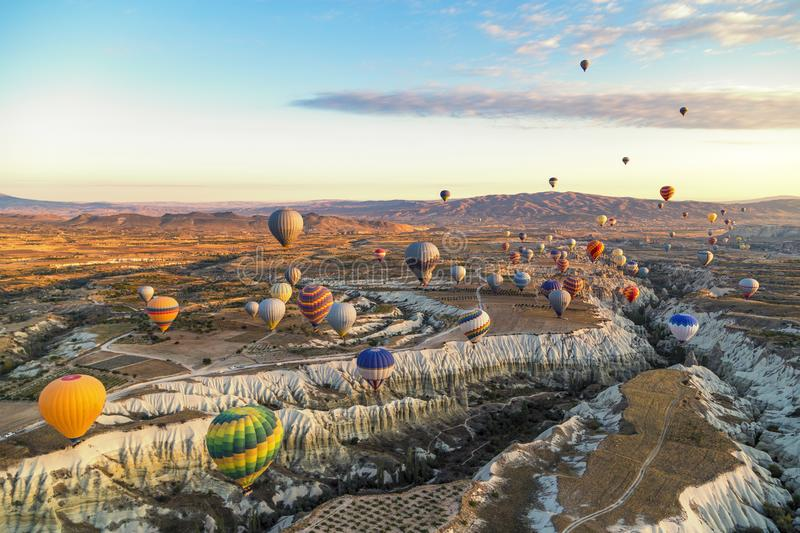 Bright and colourful hot air balloons at sunrise floating along the valleys and mountains in Cappadocia, Turkey. Floating along the valleys and mountains in stock image