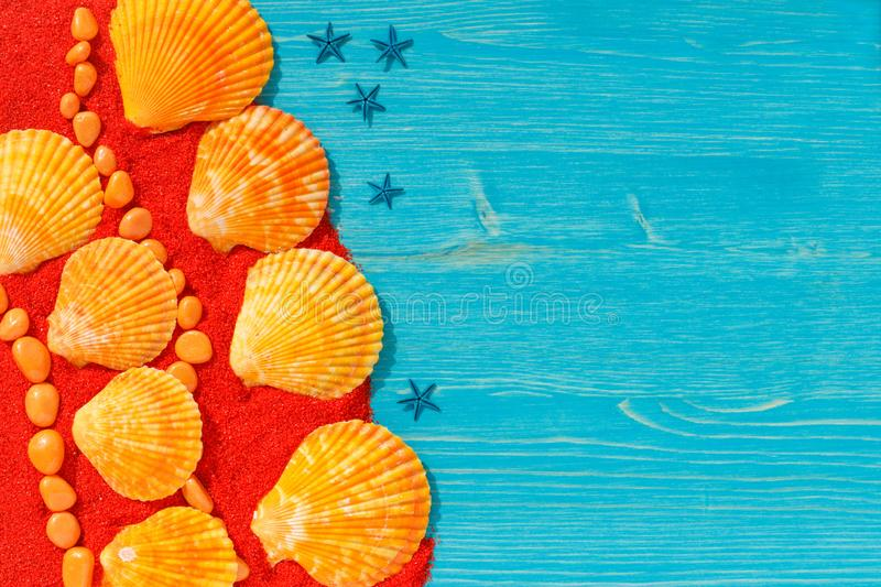 Bright colourful background with orange seashells and stones on red sand. Bright colourful picture with orange seashells and stones, blue starfishes on red sand stock photo