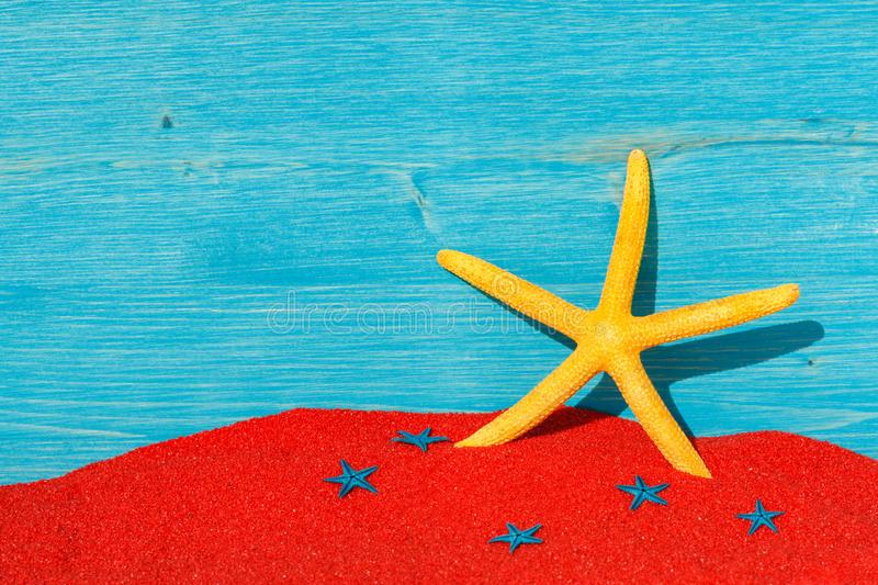 Bright colourful background with yellow starfish end red sand. Bright colourful picture with yellow starfish, red sand and a blue wooden background. Empty card royalty free stock photography