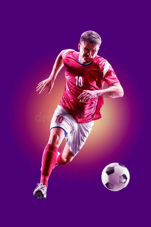 Colourful professional soccer player isolated over purple background stock photography