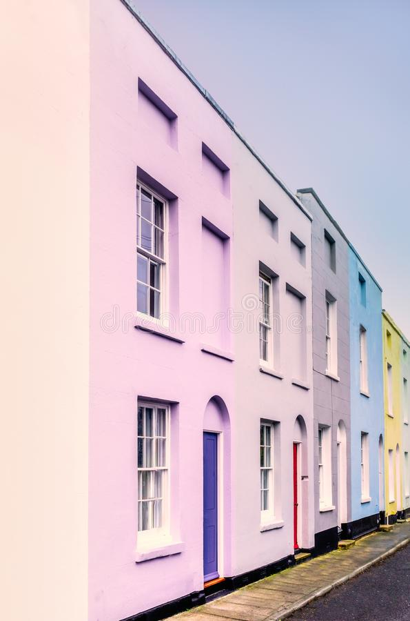 Bright colourful symmetrical row, terrace houses. Lilac, blue, yellow each with two sash windows and lunette arch above the doors royalty free stock photography