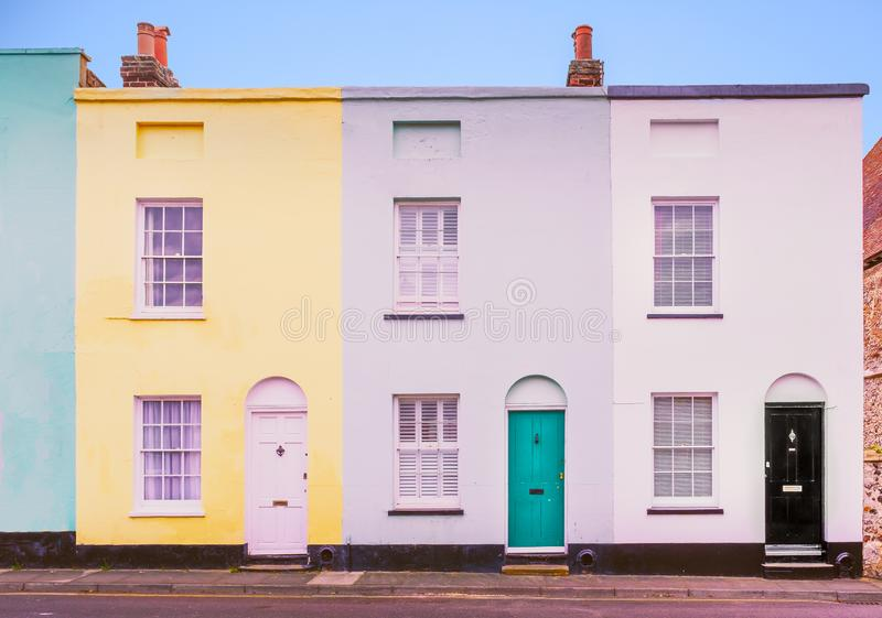 Bright colourful symmetrical row, terrace houses each with two s. Ash windows and lunette arch above the doors which also have knockers stock photography