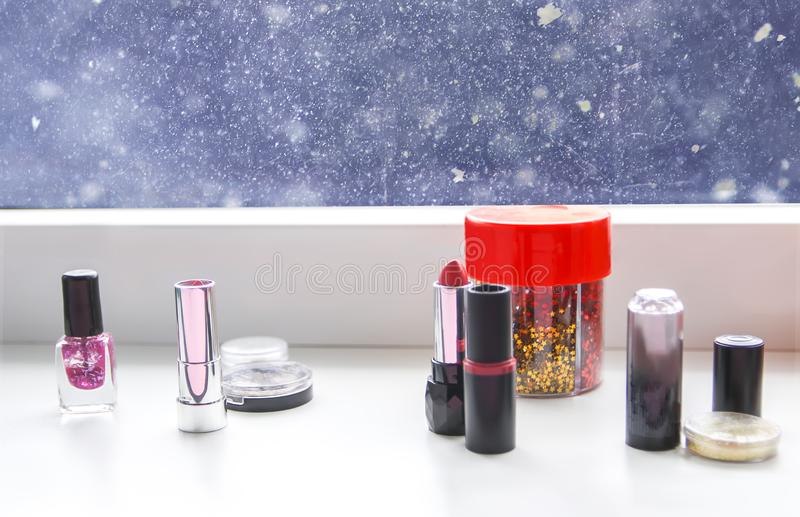 Bright composition of fashion accessories. Lipsticks, nail polish and tinsel. Objects on soft pastel background. Flat lay, top stock photo