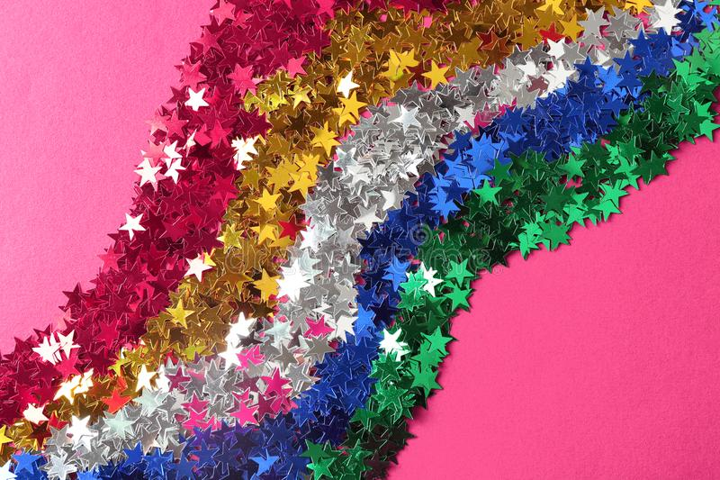Bright confetti in shape of stars on pink background stock image