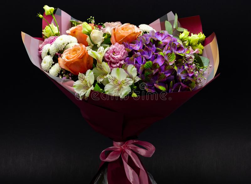 Bright contrasting bouquet assembled from hydrangea, peony rose, chrysanthemum, eustoma and alstroemeria. On a dark background stock images