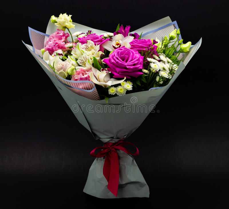 Bright contrasting bouquet of fresh flowers on a dark background stock photography