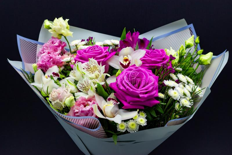 Bright contrasting bouquet of fresh flowers on a dark background stock photo