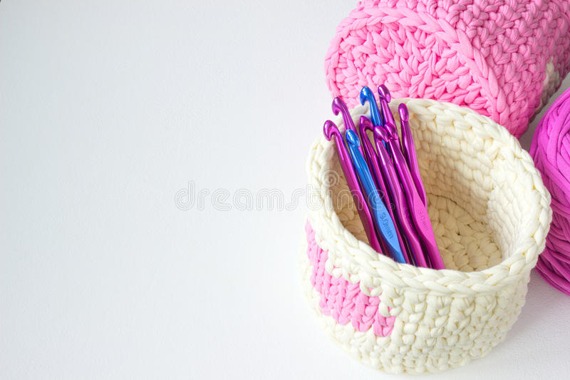 Bright crochet boxes amd crochet hooks with number. Pink and white crochet textile tutorial pattern. Thick ribbon cotton yarn royalty free stock images