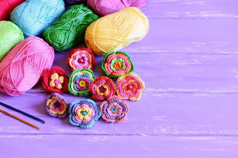 Bright crochet flowers set. Homemade crochet flowers, varicolored cotton yarn, crochet hooks on wooden background. Crochet flowers. Knitted flowers. Crocheted stock photo