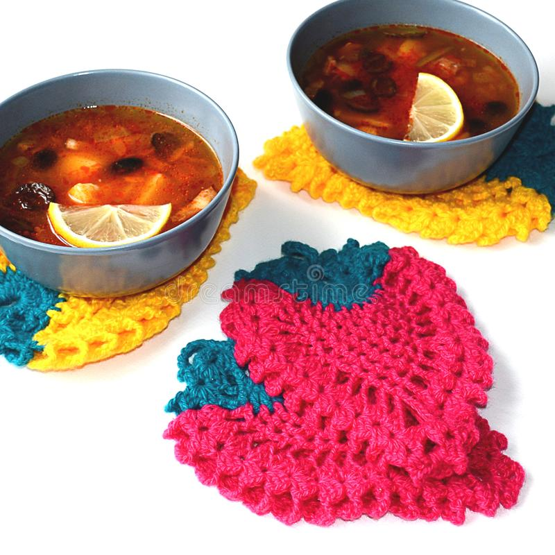 Bright crocheted kitchen pot holders in form of berries.  royalty free stock photos