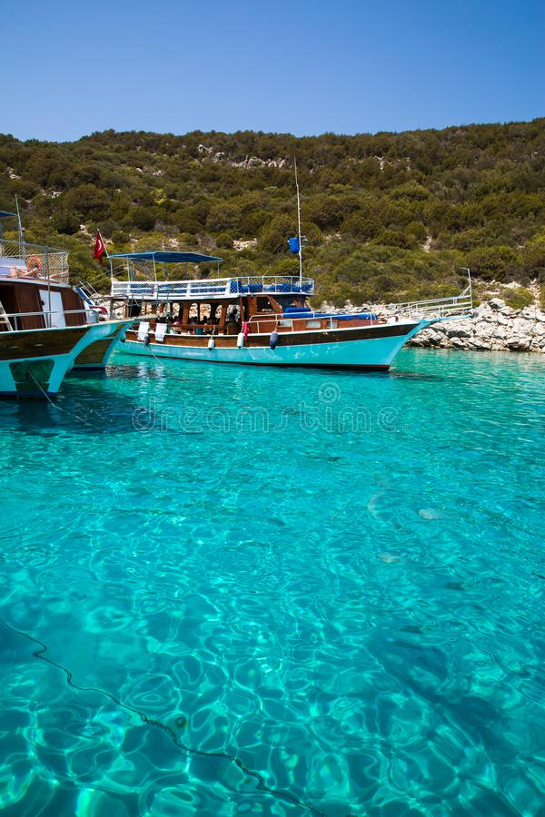 Bright crystal water of Meditteranean sea. Near Turkey and Greece borders. Touristic boats with tourists royalty free stock photography