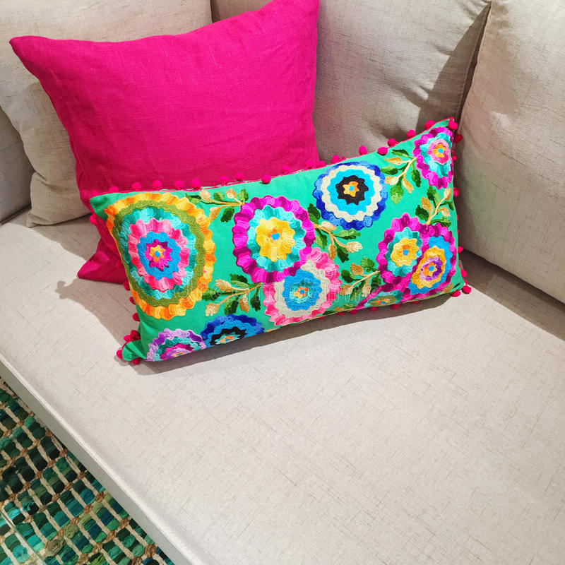 Bright cushions with floral design on a sofa. Bright pink and green cushions with floral design decorating a sofa royalty free stock image