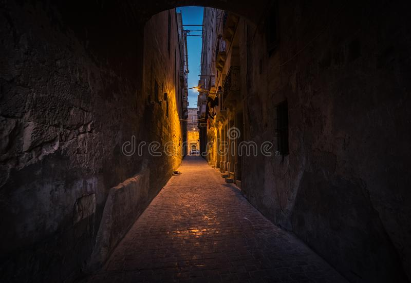 Bright and dark alleys of Valletta. The path to light. Malta. Walking at night in the old town of Valletta. ghts and darkness royalty free stock photos