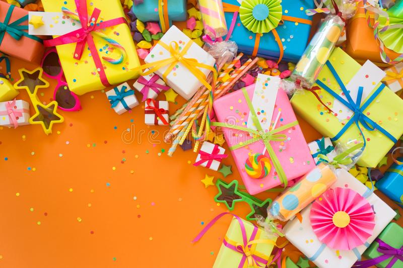 Colored gift boxes with colorful ribbons. Orange background. Gif royalty free stock images