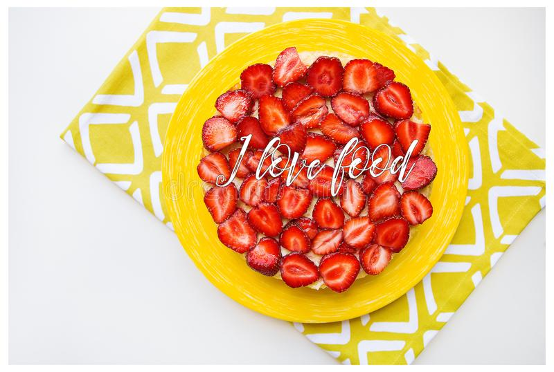 Bright and delicious strawberry cake on a yellow napkin, the inscription I love food royalty free stock photography