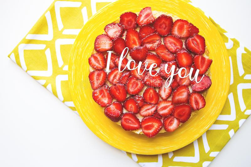 Bright and delicious strawberry cake on a yellow napkin, the inscription I love you stock photo