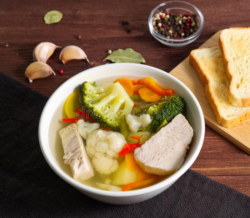 Bright dietary soup with a chiken meat, cauliflower, broccoli and other vegetable on brown wooden background, side view. stock image