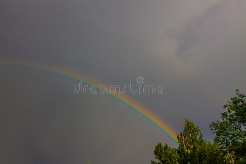 Bright double rainbow in a stormy sky. Bright beautiful double rainbow on a dark stormy sky with clouds framed by green trees stock images