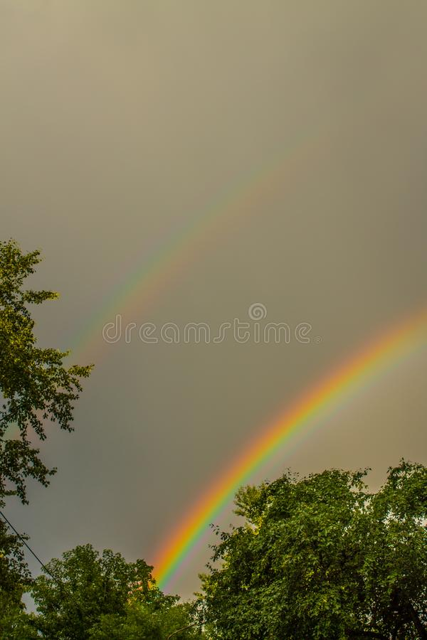 Bright double rainbow in a stormy sky. Bright beautiful double rainbow on a dark stormy sky with clouds framed by green trees royalty free stock photography