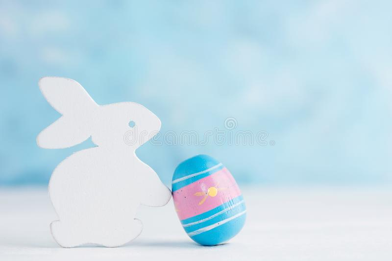 Bright Easter background: white wooden bunny with paited egg against blue wall. Holiday concept stock photos