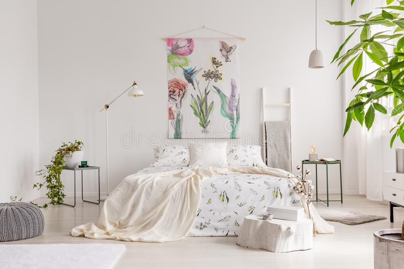 A bright eco friendly bedroom interior with a bed dresses in green plants pattern white linen. Fabric painted in flowers and birds royalty free stock image