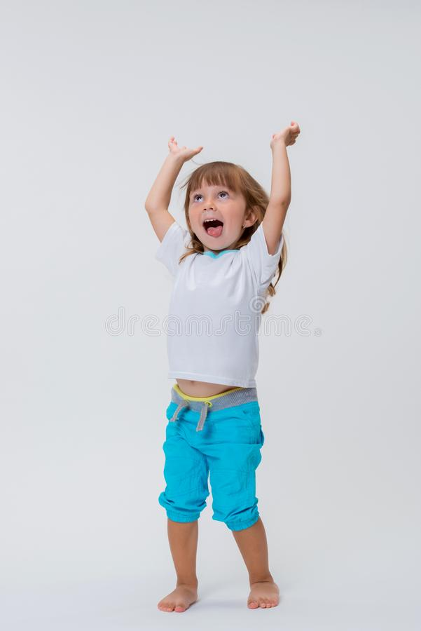 Bright emotions and positive. Little smiling girl happily jumping to the ceiling with arms up isolated on white background stock photography