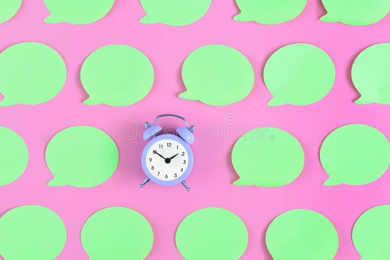 Bright, empty light green labels on a pink background. In the center is a small lilac alarm clock. Concept, beautiful royalty free stock photos