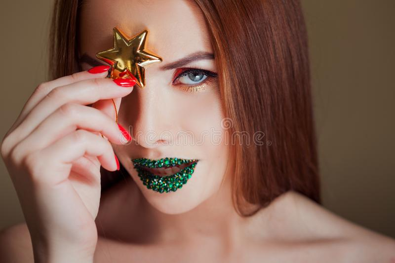 Bright eye makeup and green lips in rhinestones. Unusual look with bright red arrow on her eyes. royalty free stock photo