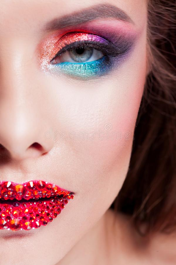 Bright eye makeup and red lips in rhinestones. Pink and blue color, colored eyeshadow. Close up stock photos