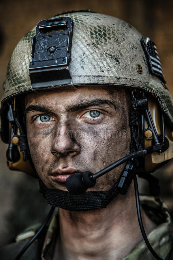 Bright eyes of young soldier. Smoked face of US Army Ranger wearing combat helmet. Closeup portrait. Bright eyes of soldier, young boy at war, sacrifice concept stock images