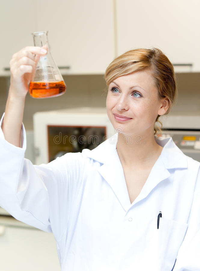 Bright female scientist looking at an erlenmeyer royalty free stock image