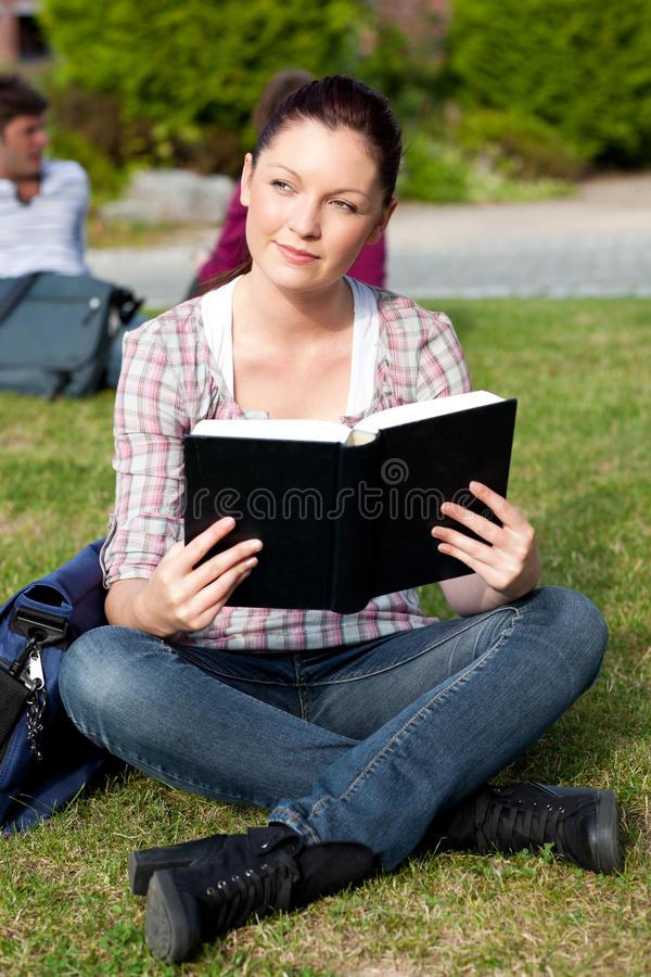 Free Bright Female Student Reading A Book On The Grass Stock Photography - 16093312