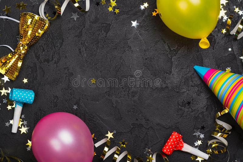 Bright festive carnival background with hats, streamers, confetti and balloons. Copy space royalty free stock photography
