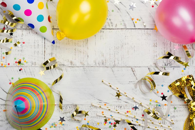 Bright festive carnival background with hats, streamers, confetti and balloons on white background. Bright festive carnival background with hats, streamers stock images