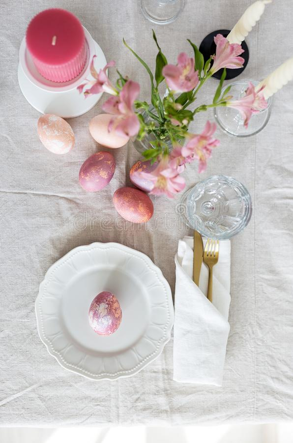 Bright festive Easter table setting with linen tablecloth, painted eggs and flowers royalty free stock photo