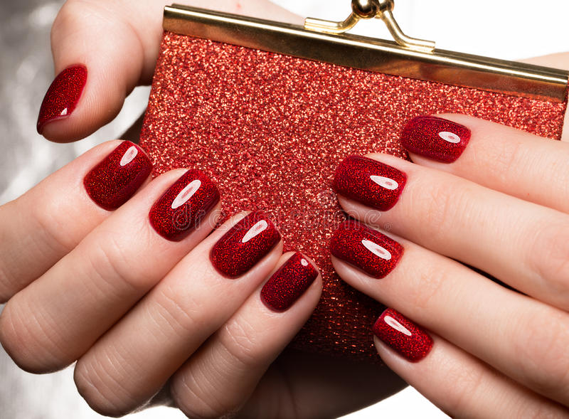 Bright festive red manicure on female hands. Nails design royalty free stock photography