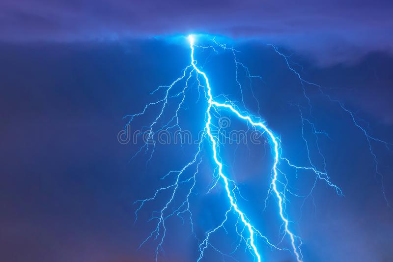 Bright flash of lightning strike during a night thunderstorm in the sky. stock photography