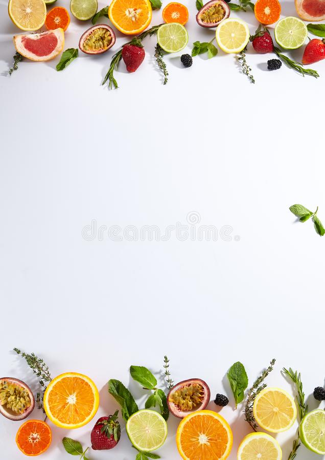 Bright Flat Lay Fruit Texture Background with Citruses. Herbs and berries top view. Lemon, lime, orange, mandarin, pink grapefruit slices, passion fruit stock photography